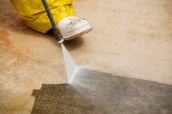 Pressure cleaning. Maintenance worker cleaning old dirty driveway with a pressure cleaner Royalty Free Stock Images