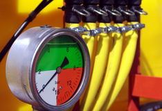 Pressure control. Pressure gauge and yellow hoses Royalty Free Stock Photo