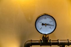 Gage. Pressure Gage with metal pipe on yellow wall background stock images