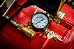 Pressure gage on red tank Stock Photo