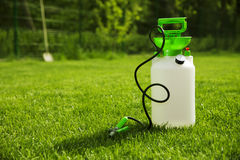 Pressure garden pump. On green grass Royalty Free Stock Photo