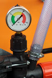 Pressure gauge. With plastic pipe and valve on orange background Stock Photo