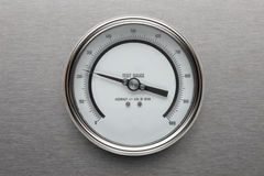 Pressure gauge. A round pressure gauge shot on stainless steel background Stock Images