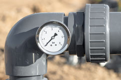 Pressure gauge and pipes. Royalty Free Stock Images