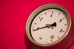 Pressure gauge on red background Royalty Free Stock Photos