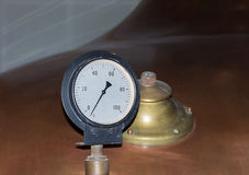 Pressure gauge to determine the pressure opposite the copper color tank with a beer factory valve royalty free stock image