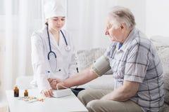Pressure measurement in elderly men Stock Photo