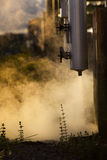Pressure pipe with smoke in industry estate against morning ligh Royalty Free Stock Image