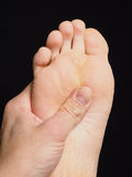 Pressure point massage under foot with thumb Stock Photography