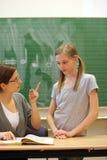 Pressure to perform by teachers. Teacher admonishes a sad child at school Stock Photo