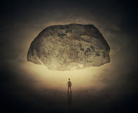 Pressure of the unknown. Surrealistic image as a man, with a bag in his back, stand in a foggy street below a huge squeezing rock. Life pressure and stress royalty free stock photos