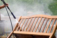 Pressure Wash Furniture/Close. Man pressure washing outdoor furniture, close up Royalty Free Stock Images