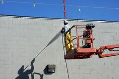 Pressure washer. Worker and his shadow pressure wash a building Stock Image