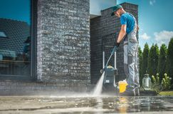 Pressure Washer Cleaning. In Front of the House. Caucasian Men in His 30s Washing Concrete Bricks Driveway in Sunny Summer Day. Cleaning Around the House royalty free stock photography