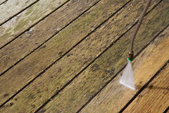 Pressure washing outdoor wooden deck Stock Photo