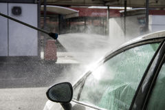 Pressure water jet over white car side window at car wash Stock Images