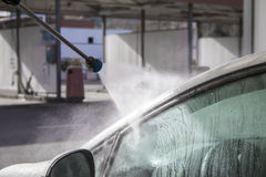 Pressure water jet over white car side window at car wash Stock Photo