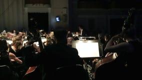 Prestaties van een symfonieorkest Een groep violisten in orkest tijdens een symfonieoverleg De leider leidt stock video