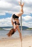 Prestazione acrobatica castana in costume da bagno sul palo per ballare Fotografia Stock Libera da Diritti