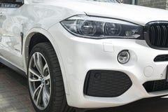 Prestazione di BMW X5 m. Ruota della lega e della gomma faro Vista frontale di un'automobile di lusso moderna bianca Dettagli di  Fotografia Stock Libera da Diritti