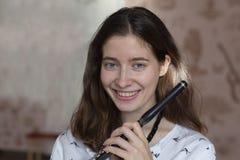 Prestazione di musica Giovane signora elegante di stordimento con lo strumento della flauto traverso fotografia stock