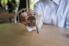Preste la casa, casa de compra, agente de la propiedad inmobiliaria que da llave al dueño imagen de archivo libre de regalías