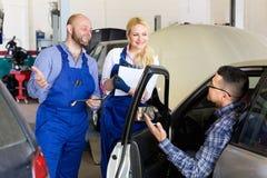 Preste serviços de manutenção ao grupo e ao motorista perto do carro Fotografia de Stock Royalty Free