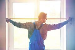 Preste serviços de manutenção ao homem perto da janela com a medida da fita imagens de stock