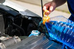 Preste serviços de manutenção ao trabalhador, derrame dentro o líquido da arruela do tanque para janelas de carro de lavagem Fotos de Stock