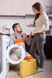 Preste serviços de manutenção ao homem perto da máquina de lavar Fotos de Stock Royalty Free