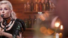 Presteert de blonde vrouwelijke saxofonist voor een publiek in een restaurant stock videobeelden
