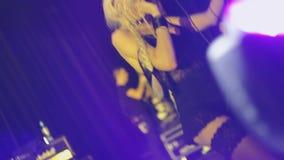 Presteert de rots vrouwelijke zanger in minikleding, kousen in nachtclub Dans op knieën met microfoon stock video