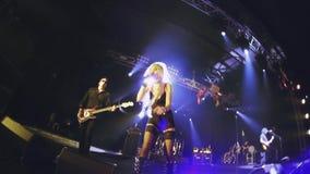 Presteert de rots vrouwelijke zanger in minikleding, rotsschoenen, kousen op stadium van nachtclub verlichting stock video