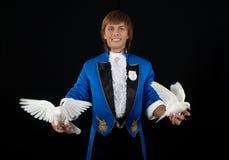Prestidigitator with white pigeons. Royalty Free Stock Photos