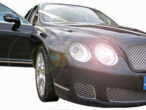 Prestige luxury wedding cars. Photo of front view of black luxurious high performance wedding car with driver's door open and headlights on Stock Images