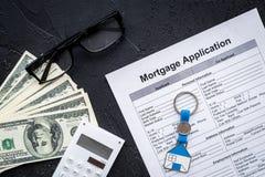 Prestito dell'alloggio Elabori un'ipoteca La richiesta di ipoteca vicino a keychain nella forma della casa ed i soldi su fondo ne Immagini Stock