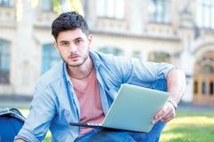 Presto per andare praticare Studente maschio sveglio che tiene un computer portatile e una r Immagine Stock