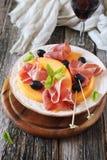 Presunto de Parma com melão e copo de vinho imagem de stock