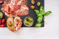 Presunto de parma do italiano com pesto, tomates e pão da manjericão imagens de stock royalty free