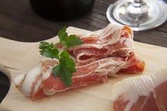 Presunto espanhol seco, presunto italiano do Prosciutto Crudo ou de Parma, corte inteiro do pé na placa de corte fotos de stock