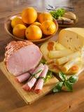 Presunto, queijo, naco e laranjas em uma tabela de cozinha. fotografia de stock