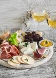 Presunto, queijo, uvas, figos, porcas, ciabatta do pão, biscoito, doce na placa de madeira branca e dois vidros do vinho branco e Foto de Stock