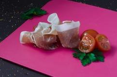 Presunto tradicional italiano, crudo cortado do prosciutto com os tomates de cereja pequenos Fotos de Stock