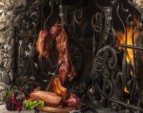 Presuntos defumados da carne de porco contra uma chaminé Fotografia de Stock Royalty Free