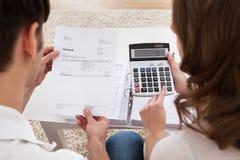 Presupuesto calculador de los pares jovenes Imagenes de archivo