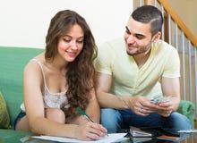 Presupuesto calculador de los pares jovenes foto de archivo libre de regalías
