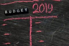 Presupuesto 2019 en bloques de madera Imagen procesada cruzada con el fondo de la pizarra fotografía de archivo libre de regalías