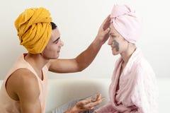 Pret het houden van paarzorgen voor de huid Zittend op de laag in handdoeken en oorzaak elkaar kleimasker op het gezicht Gezondhe royalty-vrije stock afbeeldingen