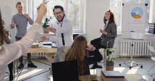 Pret jonge succesvolle zakenman die de grote viering van het carrièresucces met medewerkers delen die gekke dansgang doen op kant stock videobeelden