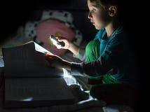 Pret Kaukasische jongen die een boek thuis lezen bij nacht met flitslicht in de hand De bedtijdverhaal van de jong geitjelezing,  royalty-vrije stock afbeeldingen